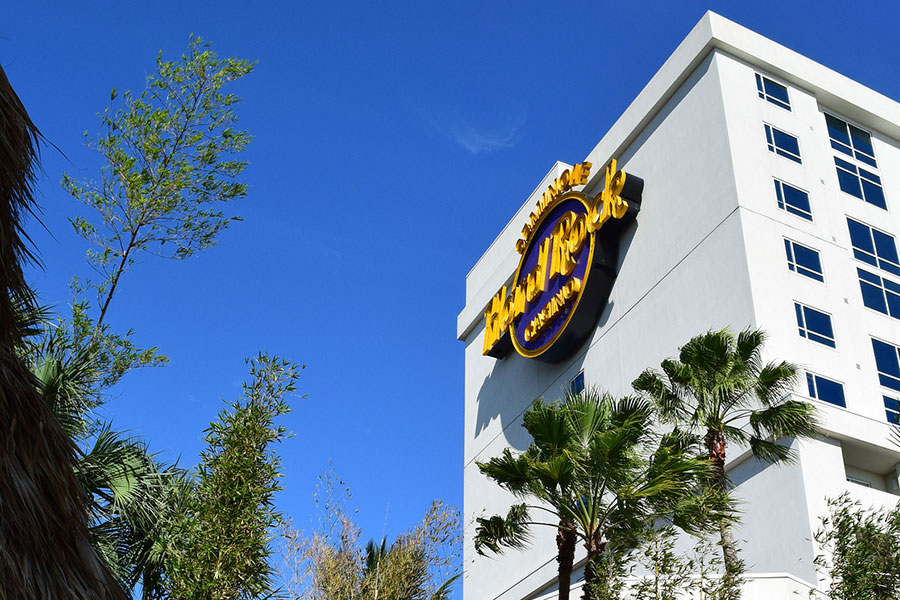 The Seminole Hard Rock Hotel and Casino logo is displayed on one side of the hotel, as seen from the tropical-themed pool area